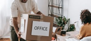 """a man carrying a cardboard box that says """"Office"""" while a woman packs in the background"""