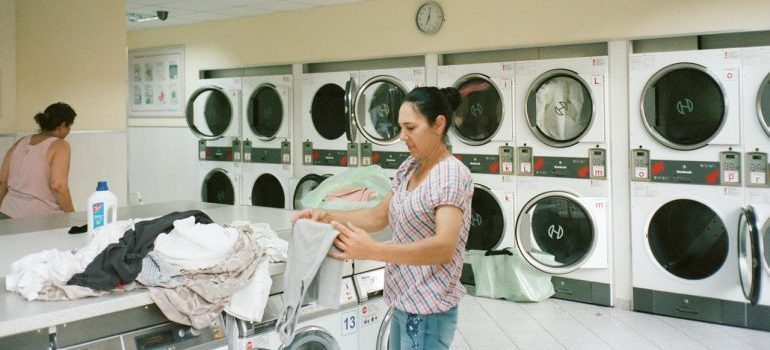 Woman inside the laundromat following one of the storage tips for summer essentials and washing her clothes