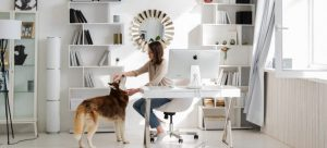 A woman with a dog, in her home-office