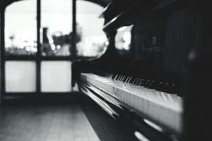 a picture of a piano with windows in the background in black and white