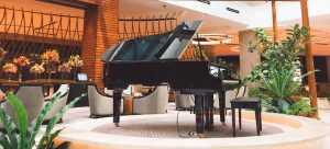 a black piano standing in the middle of an open room