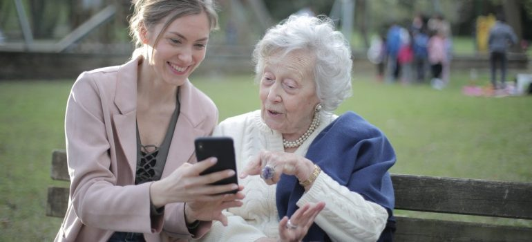 a woman showing something to her mother on the phone as something you should do to adequately prepare for moving your elderly parents across state