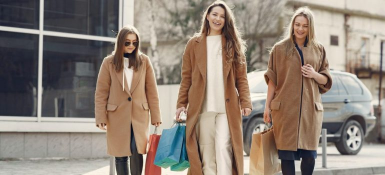 Three women in coats are walking in town and carrying shopping bags.