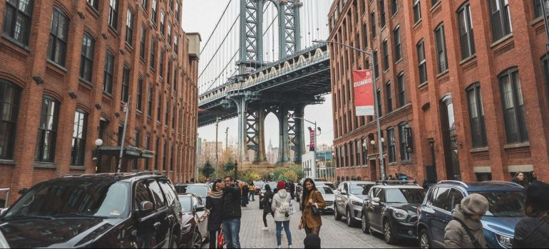 people walking through the street with the Brooklyn Bridge behind them