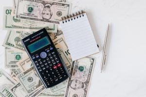 A calculator, dollar bills, and a notebook on a table