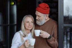 Elderly couple holding white ceramic mugs